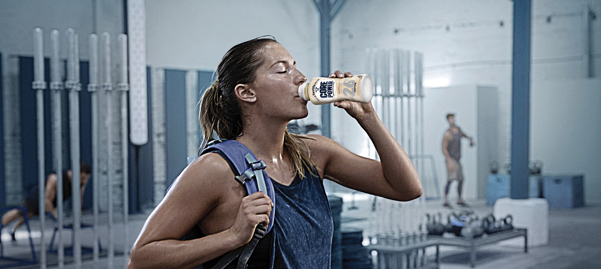 A woman drinking a bottle of Core Power Vanilla high-protein milk shake