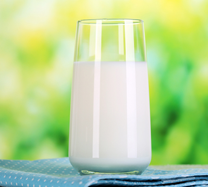 A glass of milk placed on a tablecloth
