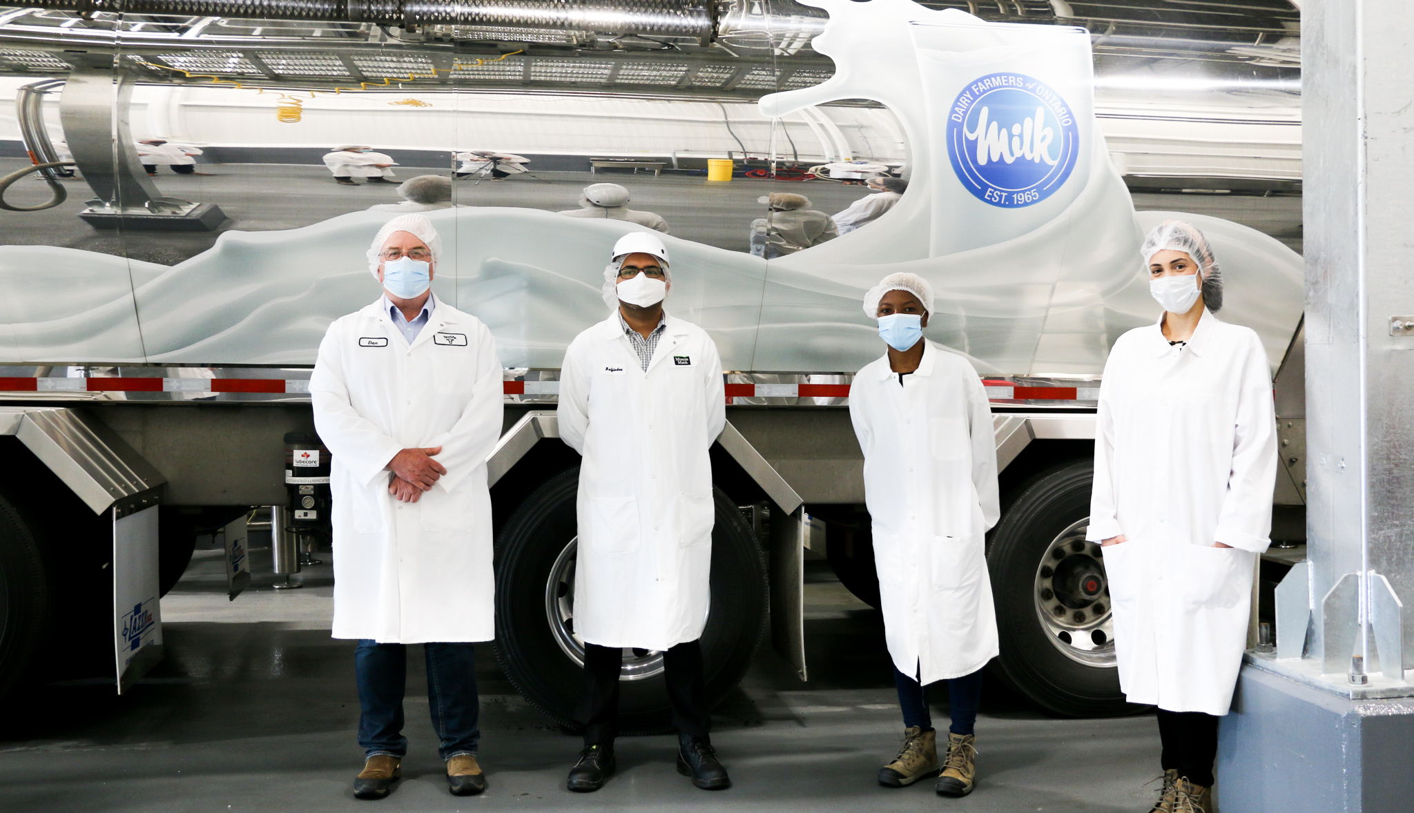 Employees stand in front of a milk truck carrying 100% Canadian milk