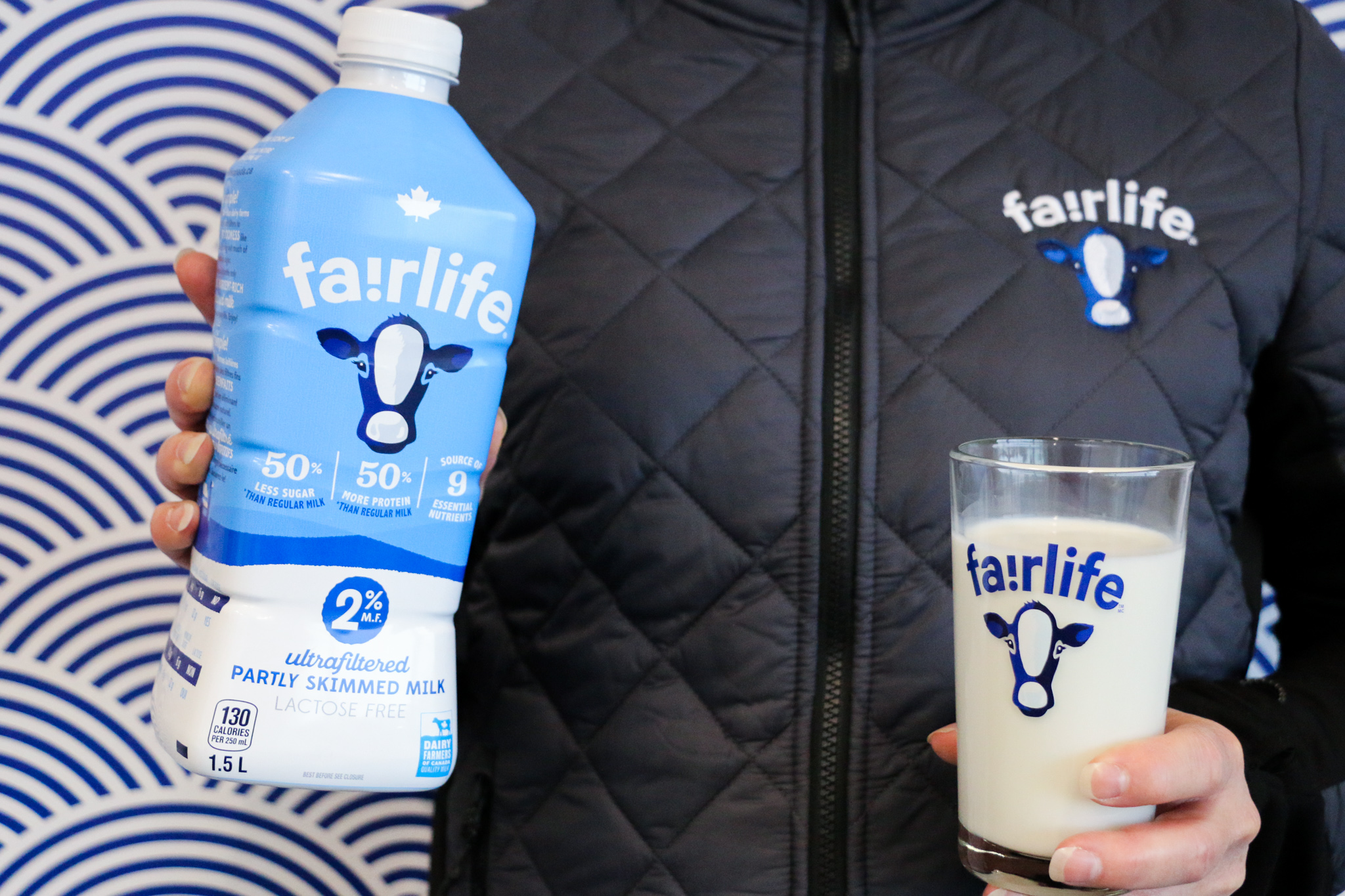 A person holding a bottle of fairlife® milk and a glass of milk